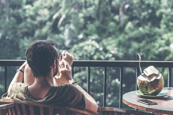 barbat care sta pe scaun pe balcon sprijinindu-si picioarele de balustrada