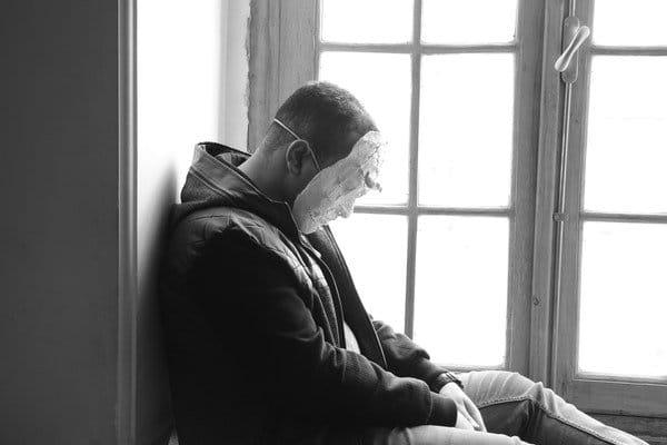 ce va zice lumea - barbat care poarta o masca, sta trist la fereatra