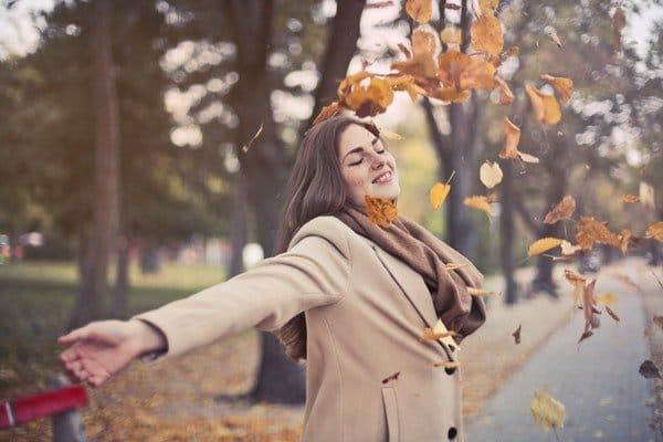 ce va zice lumea - femeie care se joaca cu frunze uscate, toamna