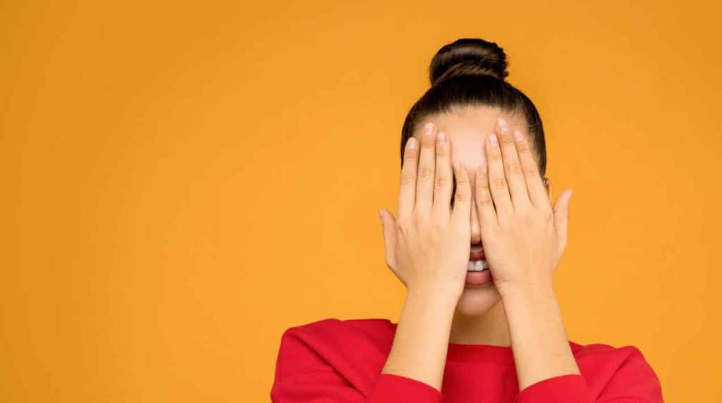 cum sa scapi de emotii, femeie isi acoprata fata cum mainile